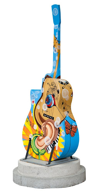 Orillia Painted Guitars downtown, blue guitar with ear and sunflower design