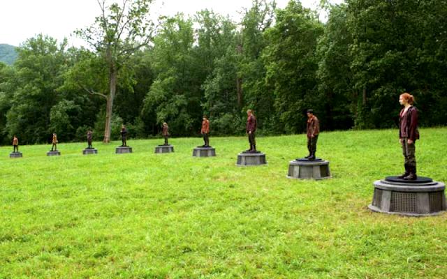 Na imagem: Cena de Jogos Vorazes com o gramado verde mostrando metade de um círculo de pessoas. Elas estão lado a lado, cada uma em cima de uma base de concreto circular, onde começam a arena.