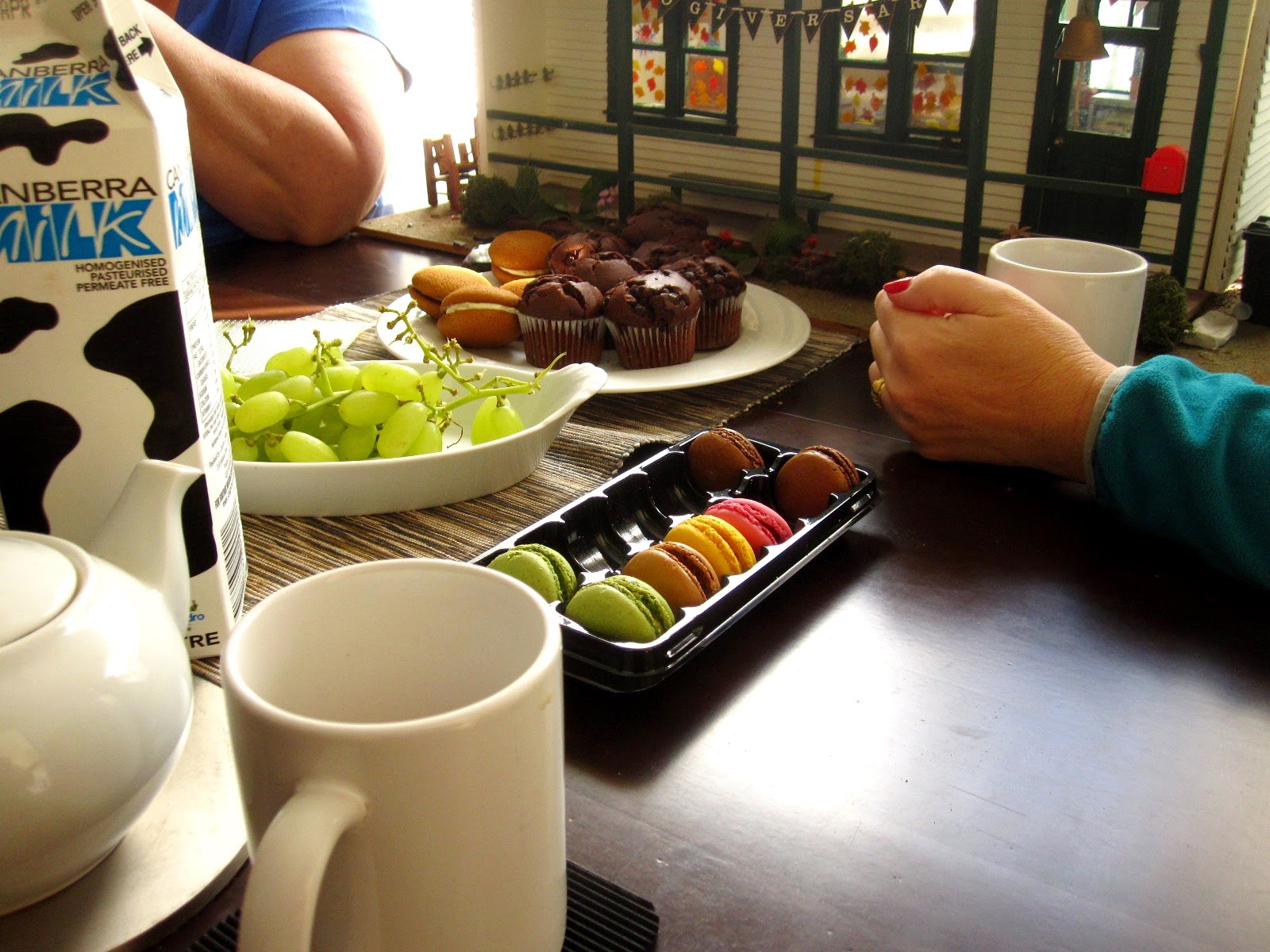 A selection of morning tea treats set out on a table in front of a modern miniatures dolls' house school