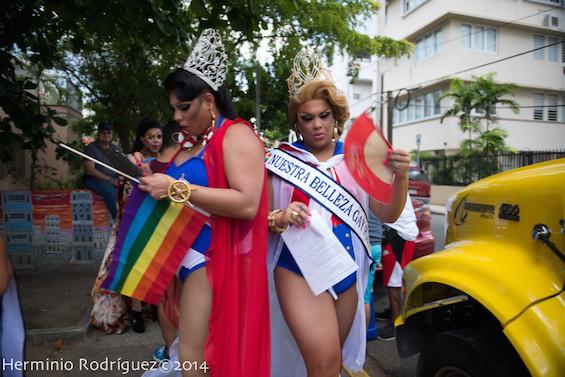 Dos reinas transformistas con la bandera arcoíris y la puertorriqueña