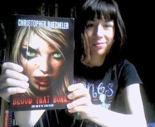 me holding a copy of The Blood That Bonds, a novel by Christopher Buecheler