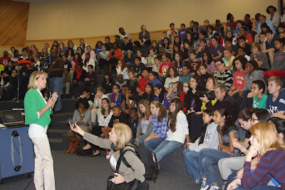 Photo of USGS staff at media event at a middle school. A woman speaks in front of a large crowd of attentive students in an auditorium. One person in the audience holds up a voice recorder towards the woman speaking.