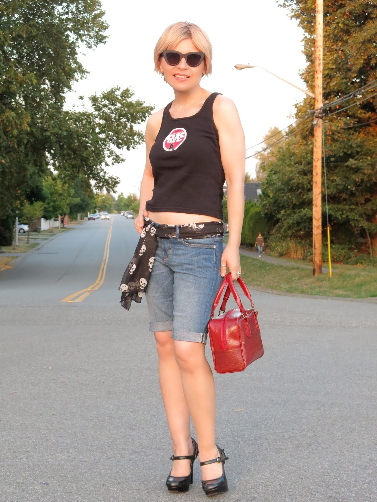 styling denim bermuda shorts with platform mary-jane shoes, a scull-print scarf, and cat-eye sunglasses