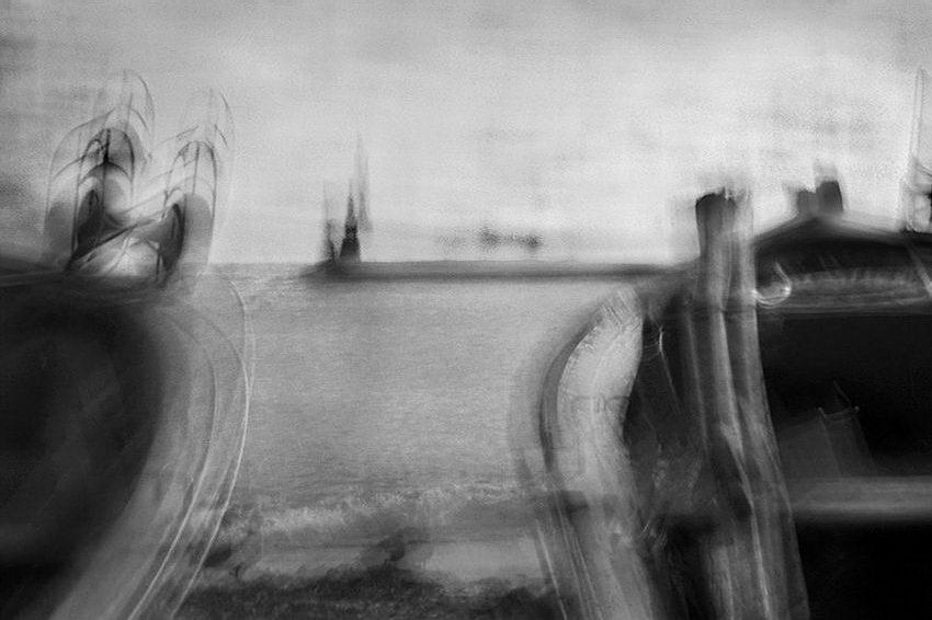 Imagens duplicadas, sobrepostas, tremidas e desfocadas. Ainda assim, consegue-se perceber uma cena junto ao mar, com o farol ao longe entre dois barcos em primeiro plano