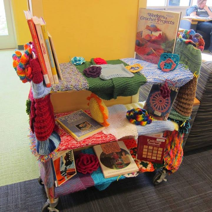 Three-shelf library book cart, covered with knit and crocheted pieces in a variety of colors and designs