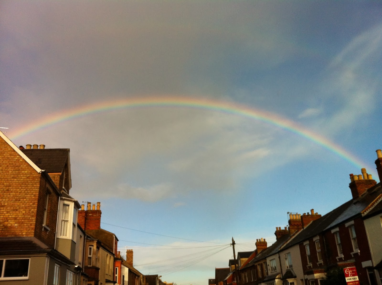 Rainbow over street of houses