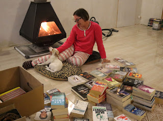 Sorting books sat in front of a roaring fire