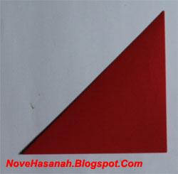 ambil sudut atas-kiri kertas origami. Lipat ke arah bawah-kanan sehingga terbentuk sebuah segitiga seperti pada Gambar berikut. Bantu anak untuk merapikan lipatan. Kadang-kadang mereka kesulitan untuk membuat lipatan di bagian sudut-sudut kertas origami