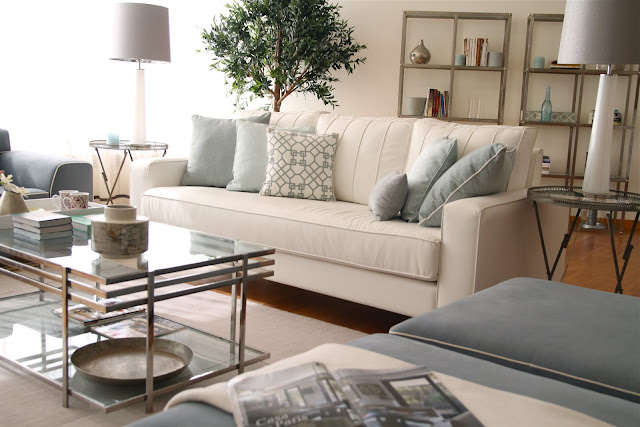 Living room with white sofa with blue and grey accent pillows, woof floor, glass coffee table with metal frame, blue chairs with white piping, round glass side tables with metal legs and a small tree