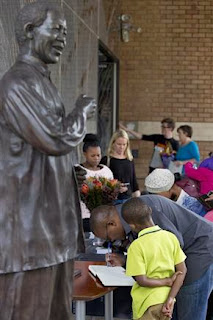 Visitors sign the condolence register next to a statue of  Nelson Mandela at the Nelson Mandela Centre of Memory in Johannesburg, South Africa.