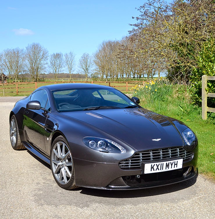 Aston Martin V8 Vantage S stationary on a country road glinting in the sun