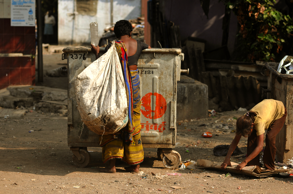 Poverty photo of a woman and a girl digging at a trash can in Mumbai, India.