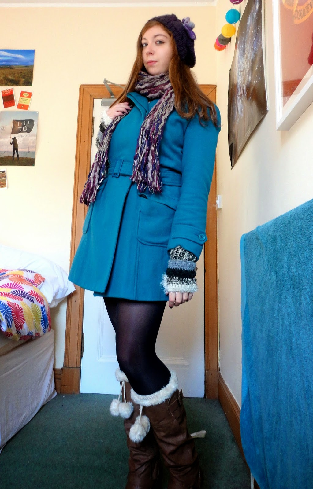 outdoor winter outfit of turquoise blue coat, brown leather boots, purple hat & scarf, fingerless mittens