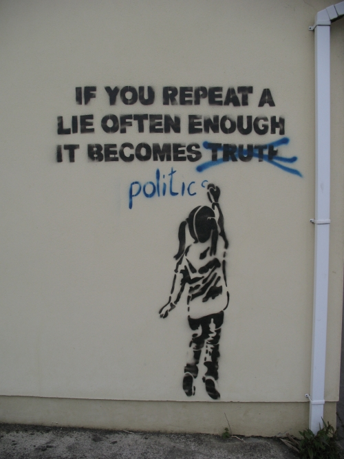 "Banksy stencil art of girl writing grafitti that says ""If you repeat a lie often enough it becomes politics"" with truth crossed out"