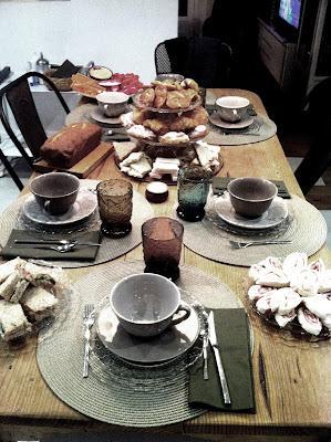 mesa puesta con juego de té y vajilla de cristal