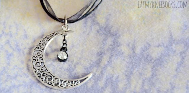 Close-up of the cutout silver crescent moon pendant and dangling gem on the Nyctophilia Crescent necklace from Poison Tragic on Etsy.