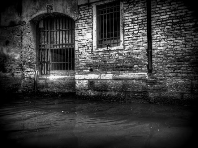 A bared window and a locked gate to some where on the canals of Venice, Italy - Black and White - HDR
