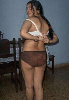 removing her bra while standing in dining room wearing panty and bra