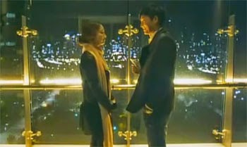 Shin Jin A and Lee Jae Ik smile at each other over the city lights.