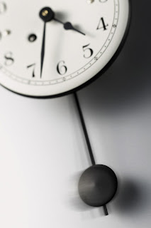 Black and white image of a clock with a pendulum swinging below it