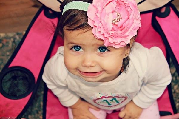 Bébé mignon fille au yeux bleu avec une jolie fleur sur la tête