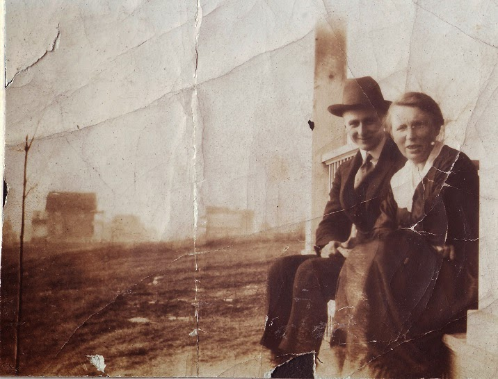 This is Mrs. Bond and her brother, sitting on the porch at 623 Fraser. The photo is looking north up the street.