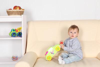 niño de 2 años con coche de juguete