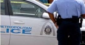 a police officer standing by side of his on duty car