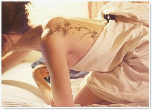 femme brune nue tatouée au dos épaule motif fleur délicate dans des draps