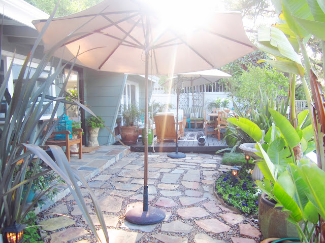 Backyard Garden with a stone pathway and umbrellas