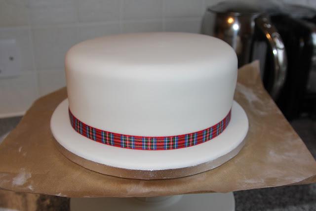 Plain iced christmas cake with tartan ribbon