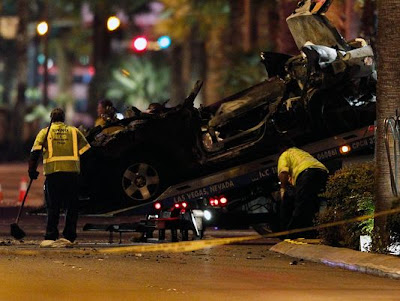Tow truck drivers clean up and tow away cars involved in a drive-by shooting on Las Vegas Boulevard in Las Vegas Thursday.