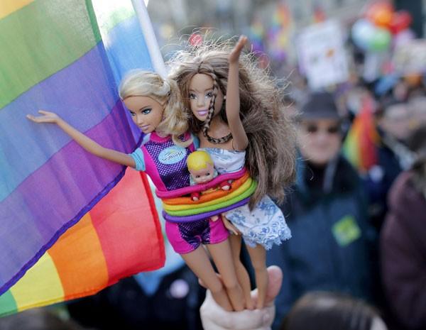Manifestante segura bonecas Barbie em marcha pelas ruas de Paris pelo casamento igualitário (Foto: Reuters)