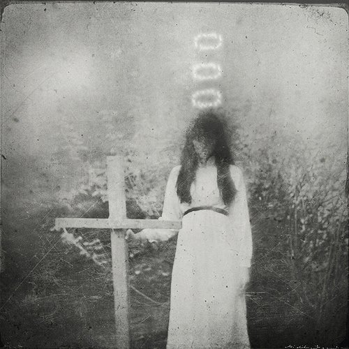 foto antigua de mujer junto a una cruz