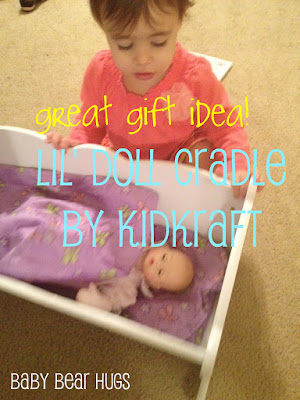 toddler with Kidkraft Lil' doll cradle