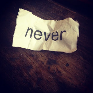 "wrinkled piece of paper with ""never"" typed on it, on a wooden table"