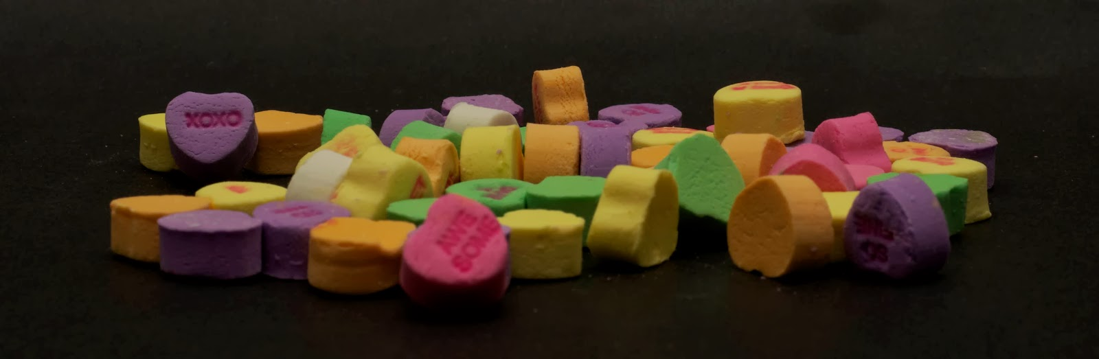 heart shaped candies with messages on black background