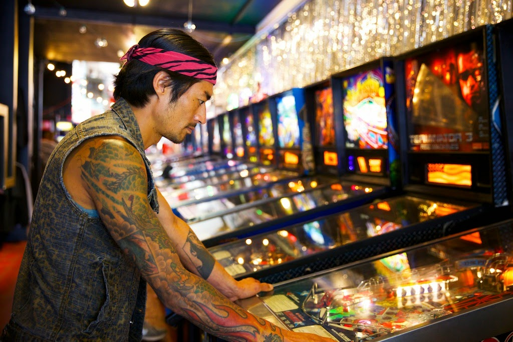 Jesse Koide of Pink Zebra SF plays pinball at Free Gold Watch in San Francisco.