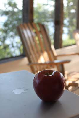 a nice red apple sitting on an apple computer
