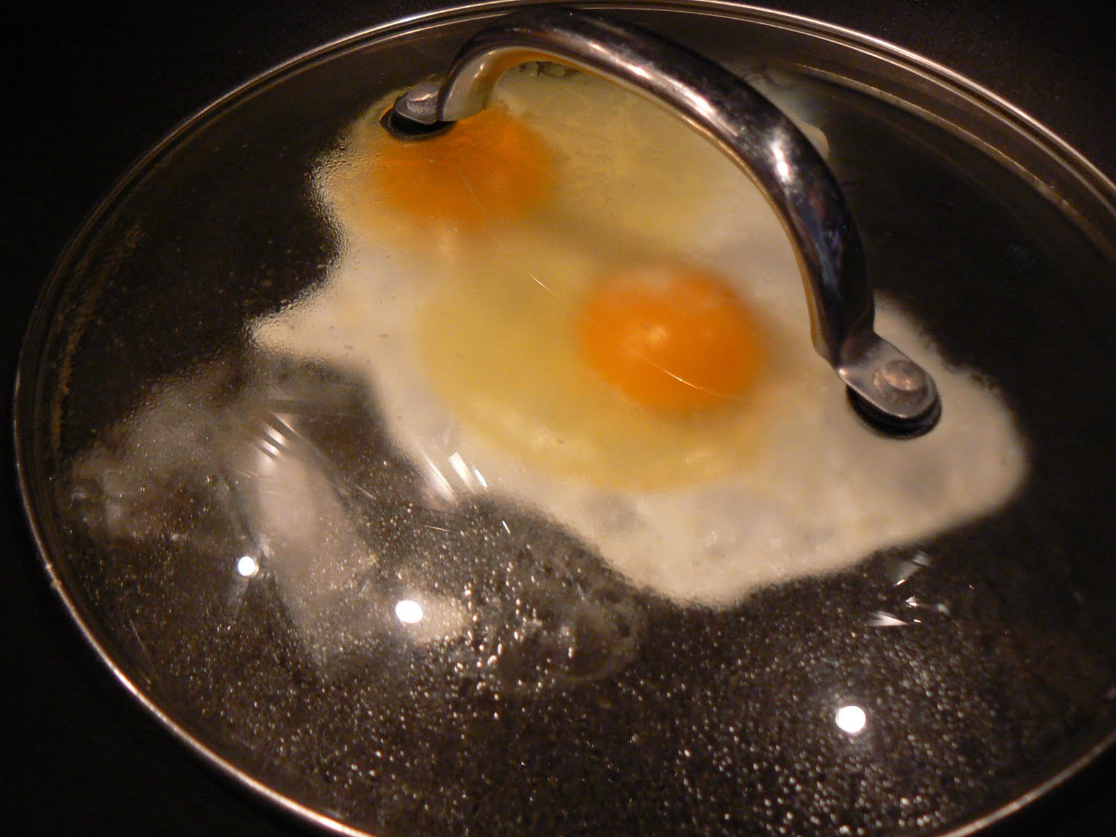 Spray your pan, crack your eggs into it, put 1 ice cube inside then ...
