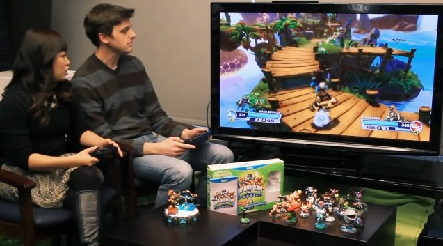 Nintendo representatives playing the Wii U version of Skylanders: Swap Force on a TV with the toys displayed at the bottom of the image