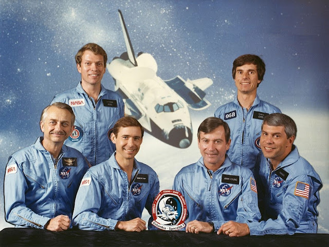 Official Portrait of the STS-9 crewmembers. Seated from left to right are Owen Garriott, mission specialist; Brewster Shaw, pilot; John Young, commander; and Robert Parker, mission Specialist. Standing from left to right are the payload specialists, Byron Lichtenberg and Ulf Merbold. Credit: NASA