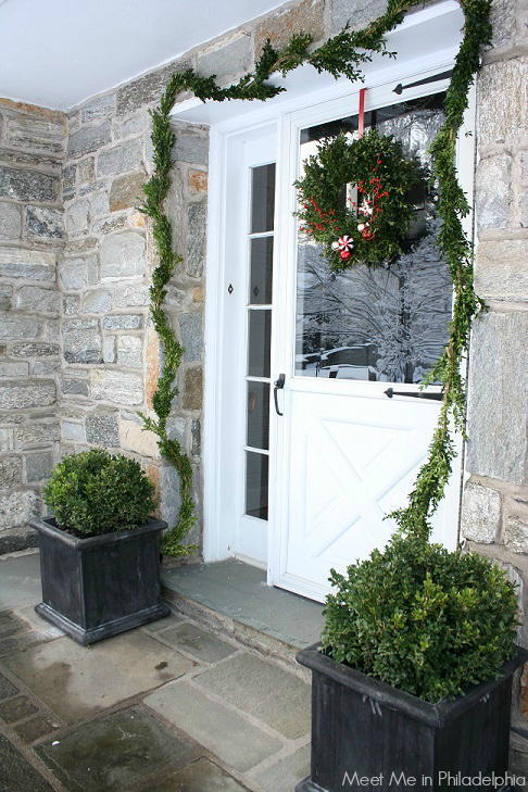 front door decorated for christmas via Meet Me in Philadelphia