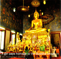 a girl pays homage to the Buddha image