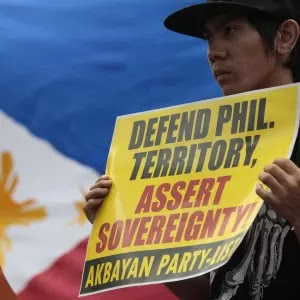 A Fililipino protester holds a slogan beside a Philippine flag during a rally outside the Chinese Consulate in suburban Makati, south of Manila, Philippines. FILE PHOTO