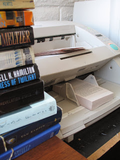 "Photo of an unbound (""chopped"") book in a scanner next to a pile of additional books ready for scanning and whose spines have been removed."