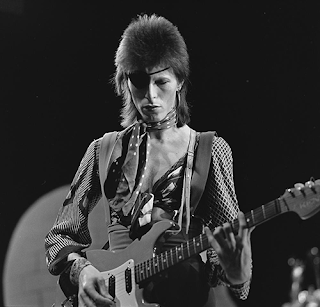 David Bowie, live on stage, wearing an eyepatch and playing a guitar in 1974
