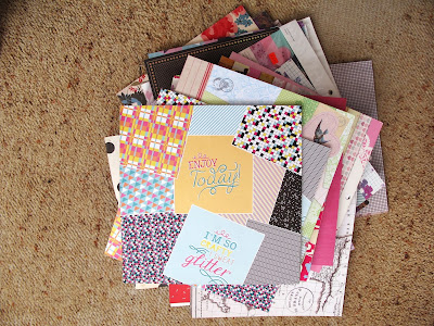 Pile of scrapbooking paper pads on the floor.