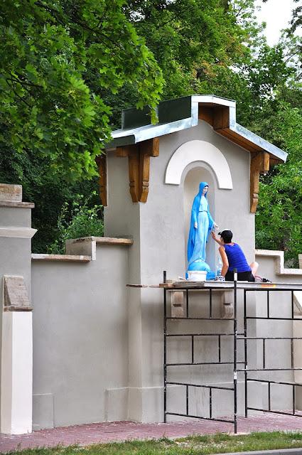 Kapliczka Matki Boskiej w murze parkowym, prace konserwacyjne - ostatnie pociągnięcia pędzla. Foto. 2013 r. KW.