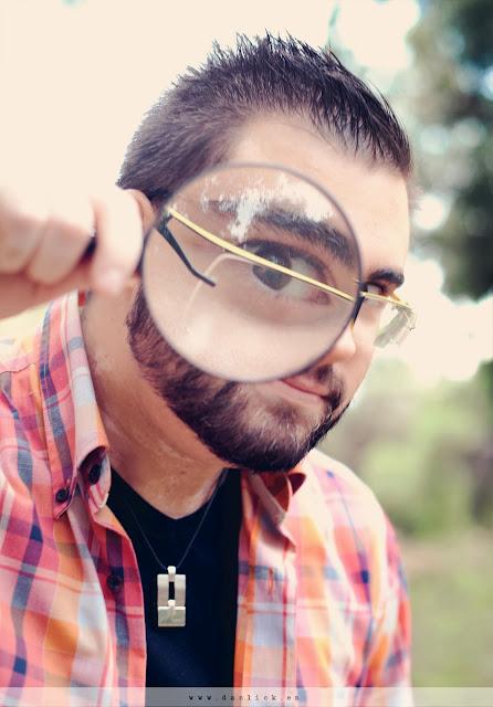 novio juega con una lupa en la sesion de foto preboda en la naturaleza